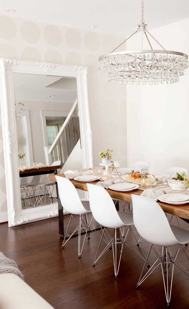 Essa sala que mescla o moderno com o retrô clássico e sofisticado apostou no uso de um espelho veneziano apoiado no chão
