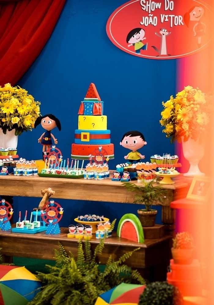 Uma bela mesa de madeira, itens decorativos, um bolo temático e bonecos com os personagens principais são suficientes para fazer uma linda decoração Show da Luna.