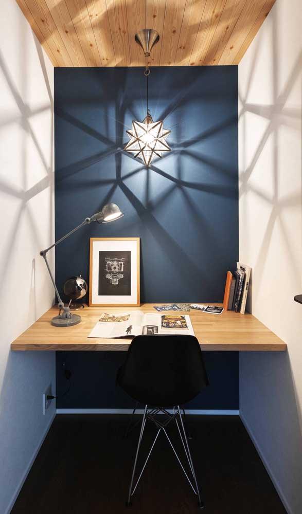 A parede azul deu um toque todo especial para a escrivaninha suspensa de madeira clara