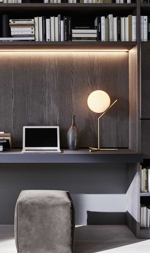 Escrivaninha suspensa preta. Repare que o puff usado junto ao móvel pode ser guardado sem ocupar espaço