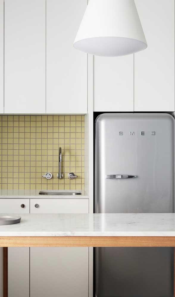 Na cozinha de marcenaria branca, a geladeira retrô prata se destaca