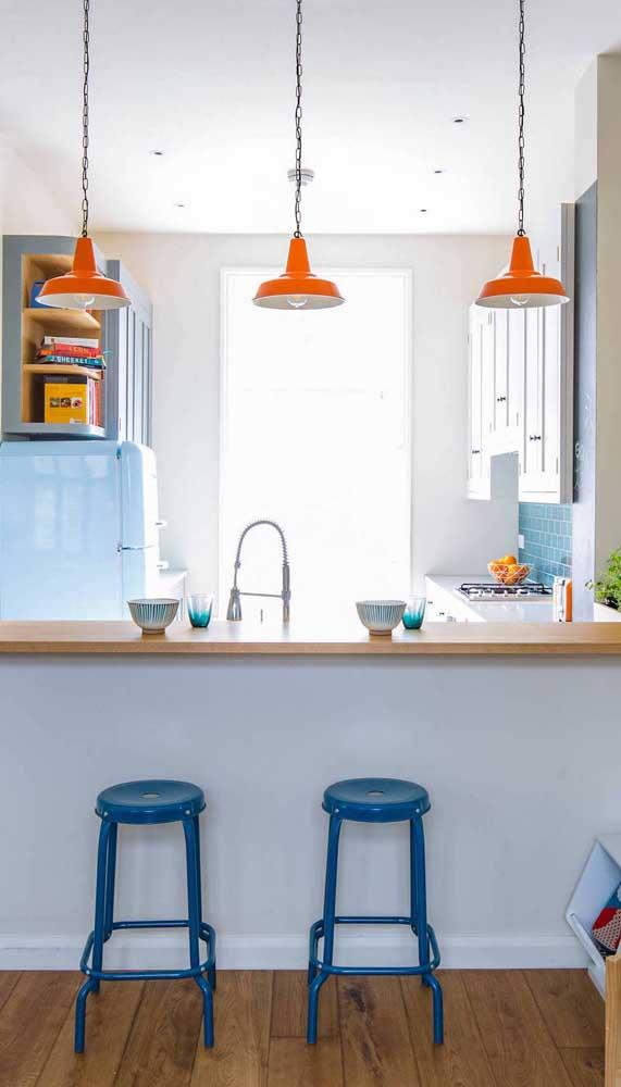 Que tal apostar em uma decor de cores complementares? Para isso, invista em uma geladeira retrô azul contrastada por luminárias laranjas, por exemplo