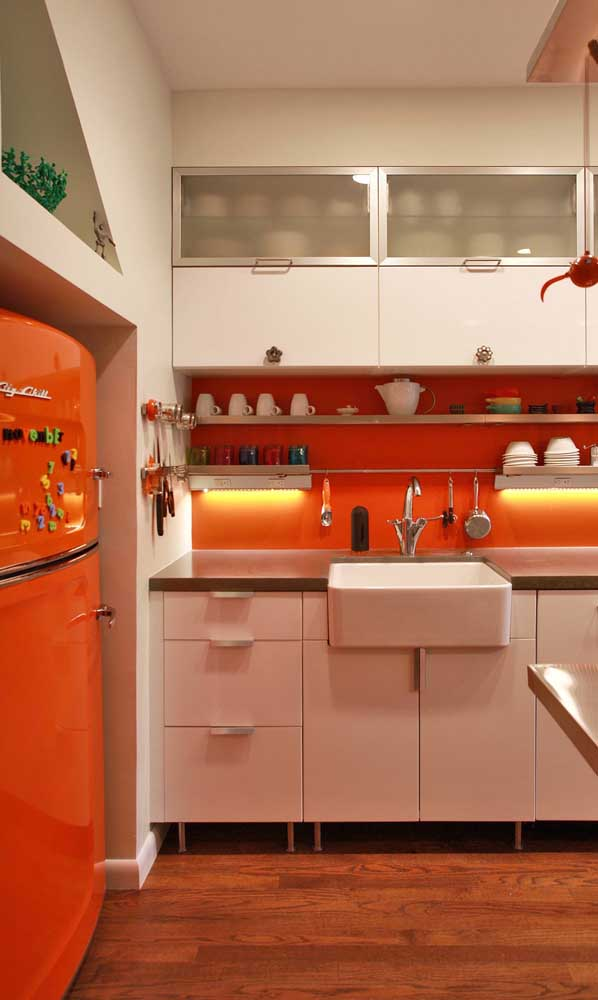 Geladeira laranja na mesma cor da faixa de parede acima da pia
