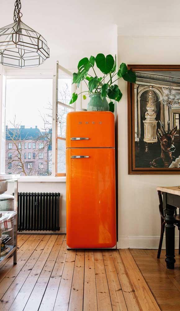Lindo contraste de cores entre a geladeira retrô laranja e as folhas de verde intenso da planta