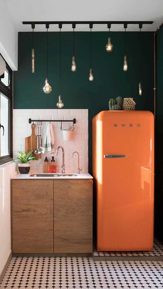 Olha que inspiração: geladeira retrô laranja na cozinha pequena de parede verde escuro e piso preto e branco