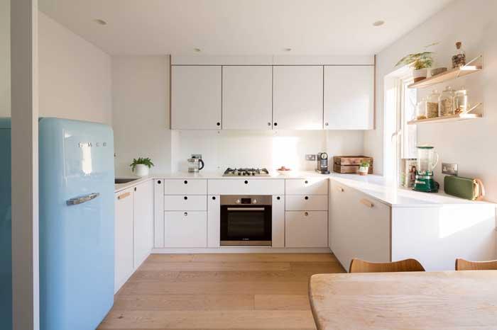 A cozinha toda branca tirou vantagem da geladeira retrô azul claro