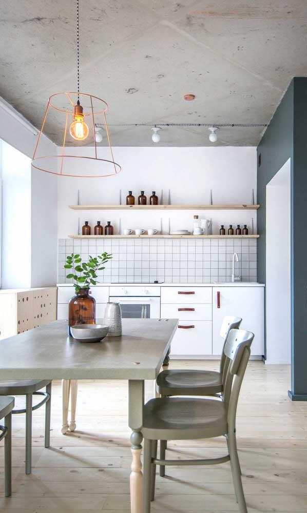 Essa cozinha integrada à sala de jantar traz traços da decoração industrial, sobretudo no pendente aramado