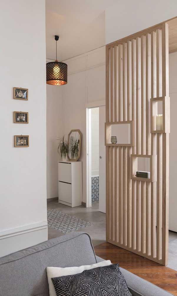 Aqui, a divisória de madeira com nichos prolonga o corredor