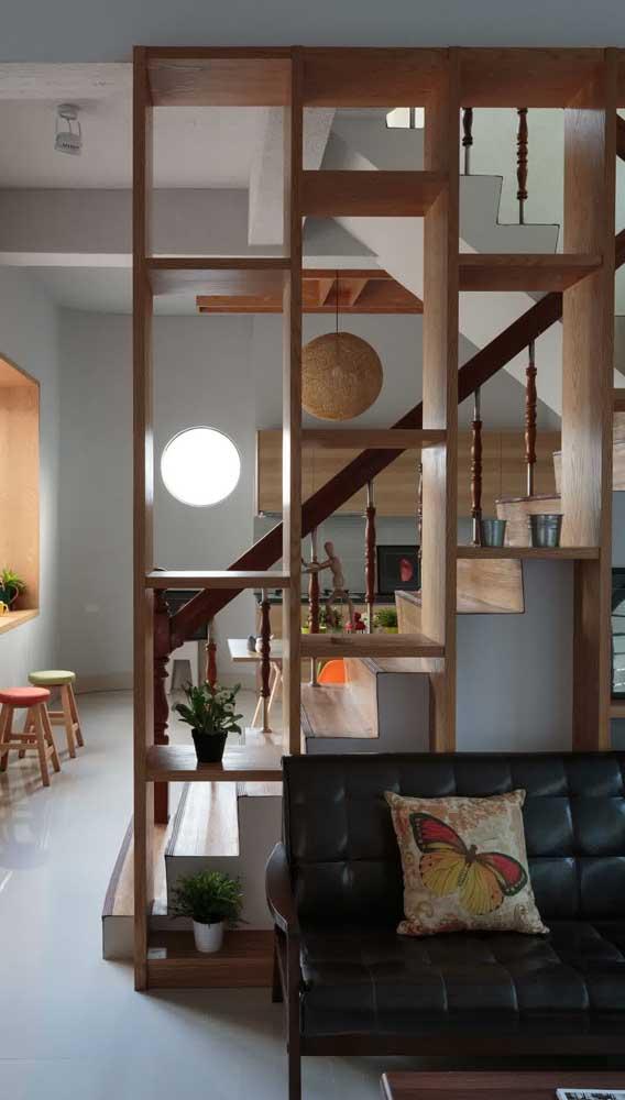 Divisória de madeira com nichos acompanhando a escada