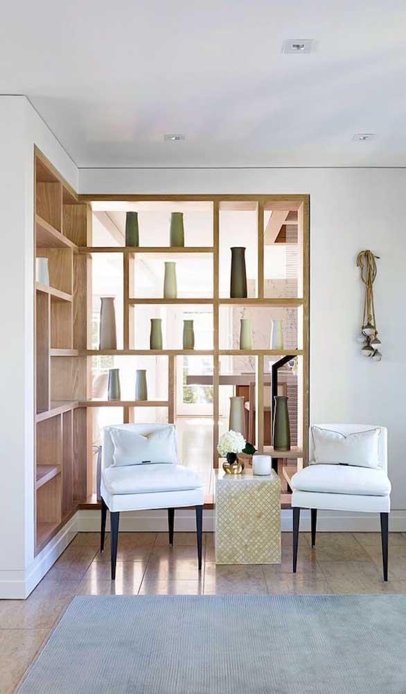 Nessa sala, a estante se prolonga na parede oposta e se torna uma divisória de madeira vazada super original