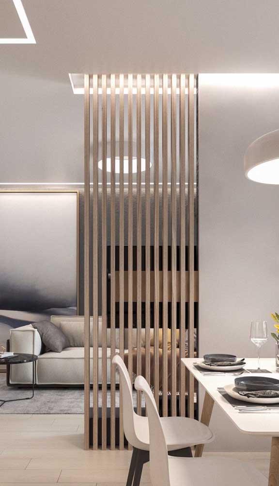 A iluminação embutida valorizou ainda mais a divisória de madeira na sala de jantar