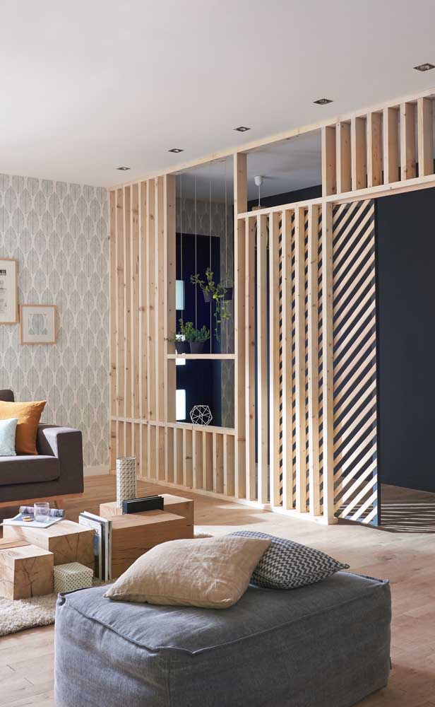 Aqui nessa sala de estar, a divisória de madeira de pinus também tem função de estante