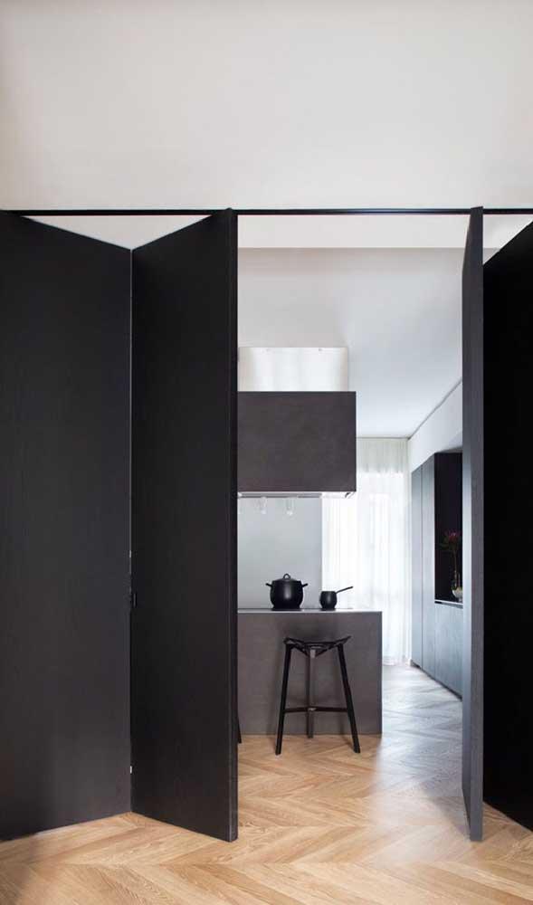 Para deixar a cozinha escondidinha foi usada uma divisória de madeira inteiriça com abertura semelhante a de uma porta dobrável