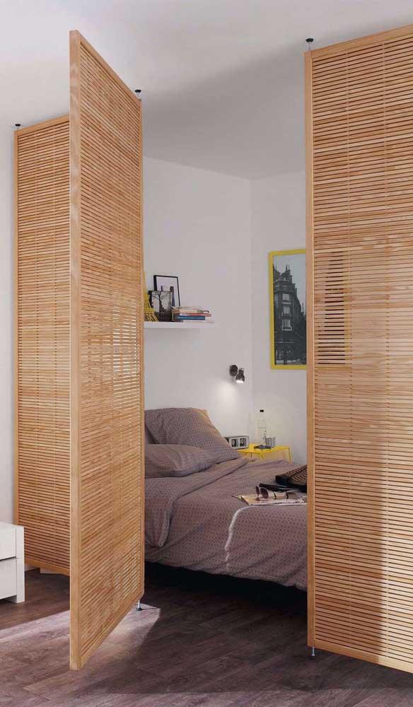 Divisória de madeira com cara de biombo e abertura de porta