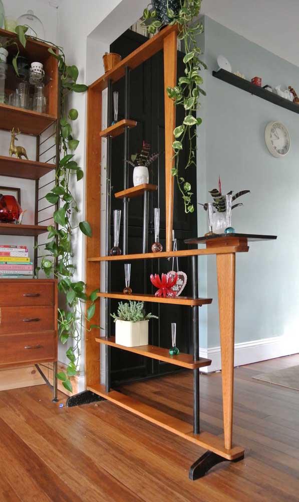 Aqui, a divisória de madeira com prateleiras possui uma função super decorativa