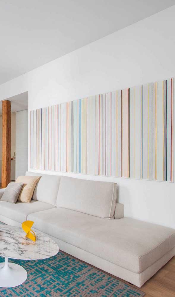 Parede listrada na sala de estar. Destaque para a variedade de espessura das listras e das cores suaves usadas na composição