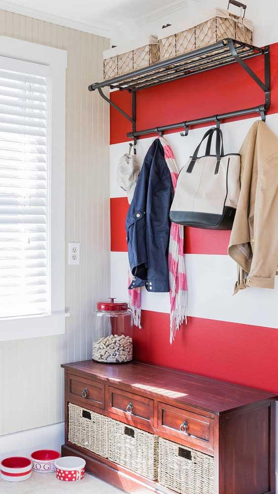 Um charme essa parede no hall de entrada com listras largas em vermelho e branco