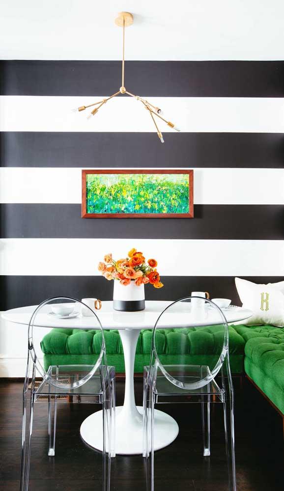 Super contemporânea essa sala de jantar com parede listrada em preto e branco. Os detalhes em verde esmeralda dão o toque final a proposta