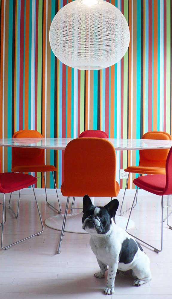 Sala de jantar com parede listrada colorida. Repare que as cadeiras acompanham a cor de uma das listras