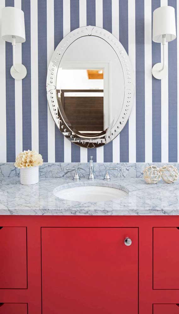 Lavabo com papel de parede listrado em tom de azul jeans. Para completar, o espelho de moldura provençal