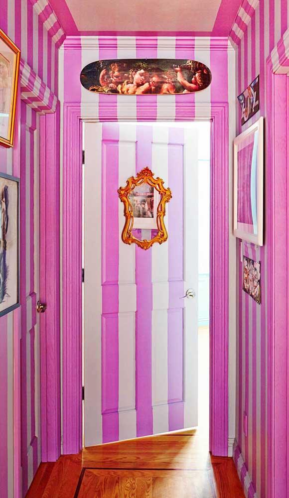 Uma decor ousada no corredor: paredes listradas em tom de rosa pink realçadas pelos objetos decorativos de estilo veneziano