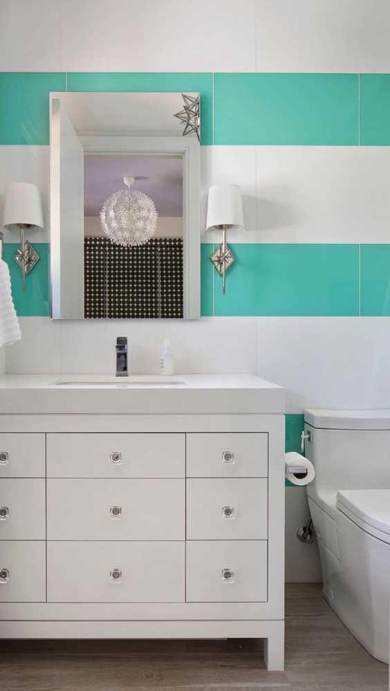O banheiro de decoração clean ganhou uma parede com listras em tom de verde água