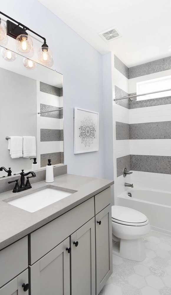 E para o banheiro foram escolhidas pastilhas de vidro cinza para formar as listras na parede da área do banho