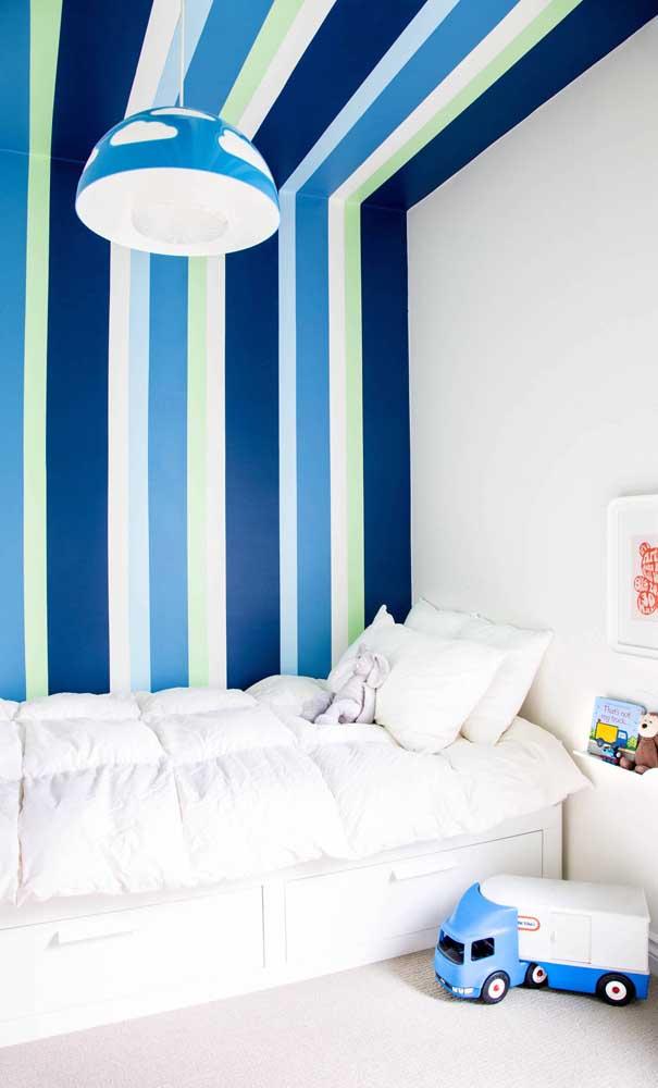 Quarto infantil com parede listrada em azul e verde. Repare que a pintura ocupa também o teto do ambiente