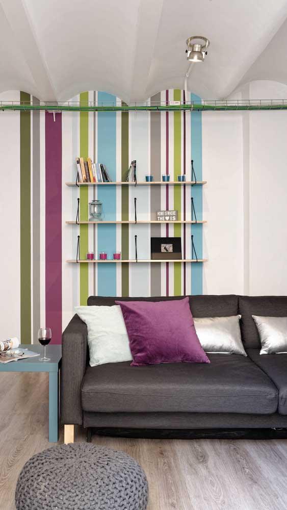 Nessa sala, a almofada sobre o sofá conversa diretamente com as listras da parede aos fundos