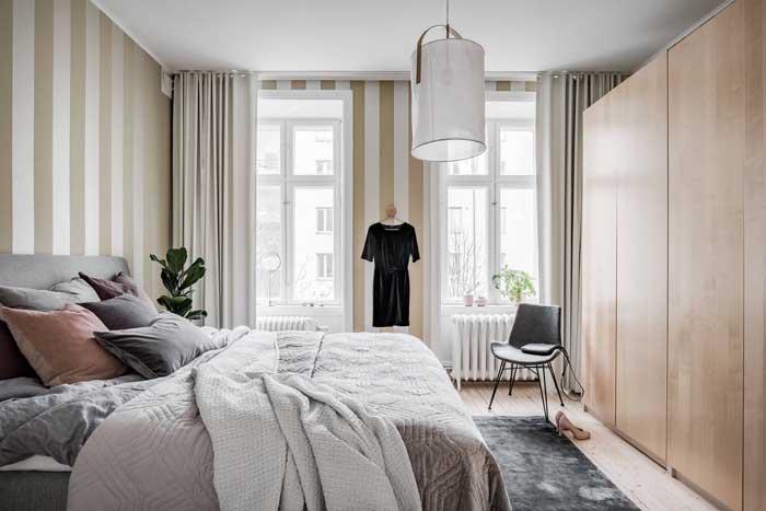 Já o quarto do casal apostou na elegância das listras em bege e branco para revestir as paredes