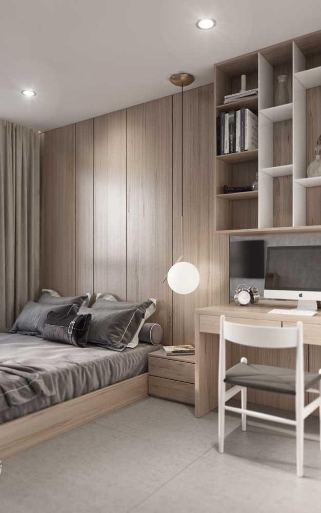 O revestimento de madeira traz conforto e acolhimento para esse quarto de solteiro