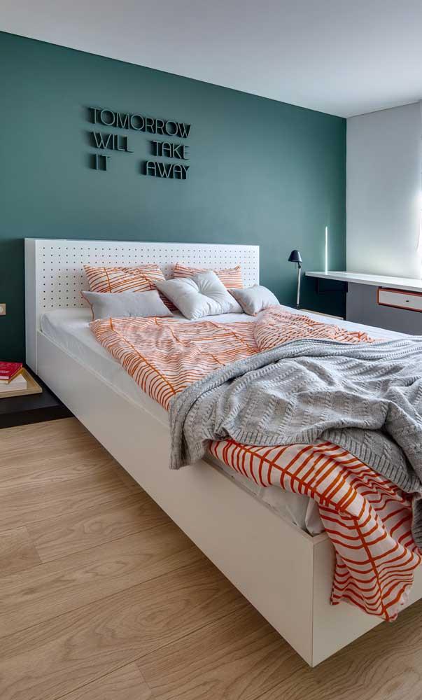 Nesse quarto de solteiro quem dita as regras é o verde azulado na parede e a cama gigante posicionada bem no meio do quarto