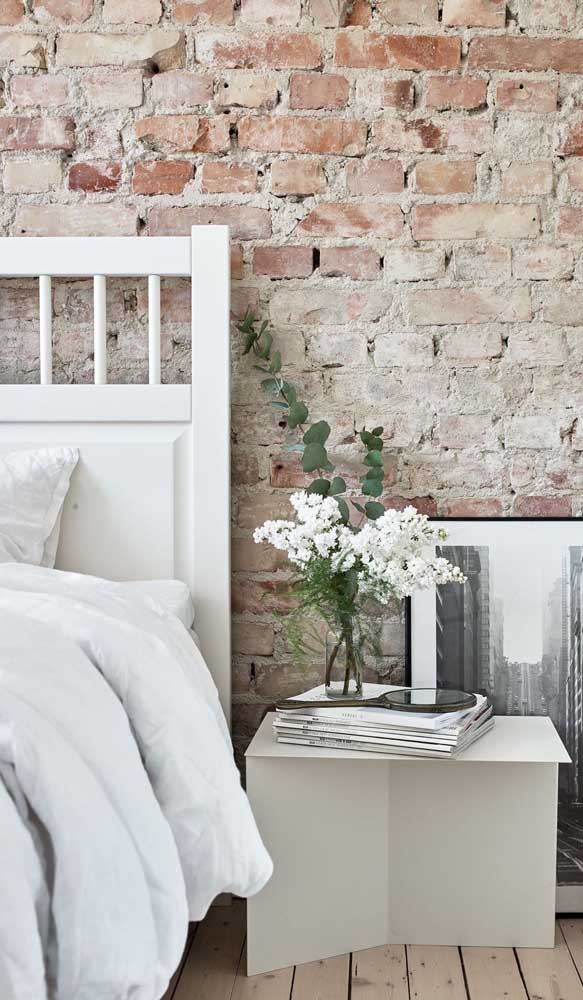 Lindo contraste entre a parede rústica de tijolinhos com o criado-mudo de design contemporâneo