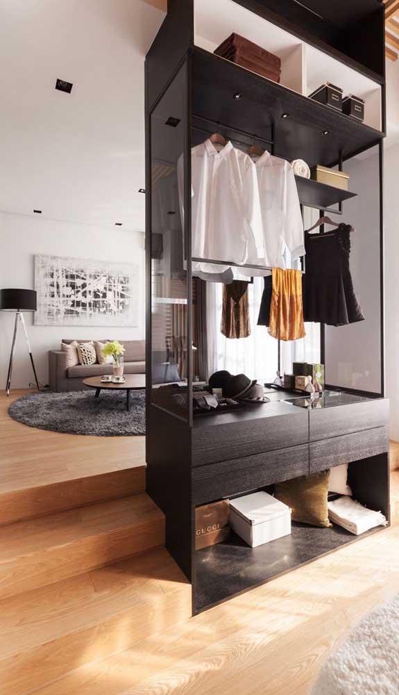 Aqui, o guarda-roupa aberto fica entre o quarto e a sala
