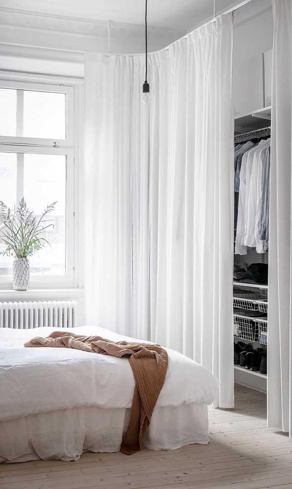 Guarda-roupa aberto com cortina. Repare que a mesma cortina usada na janela se estende até o armário