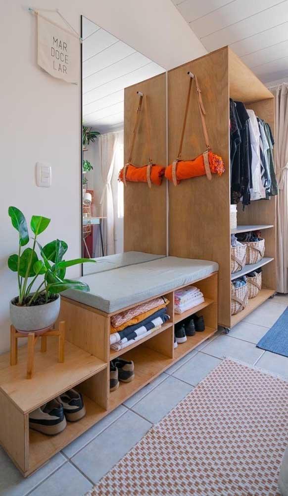 Guarda-roupa aberto feito em madeira. Destaque ainda para a sapateira que segue a mesma proposta do armário principal