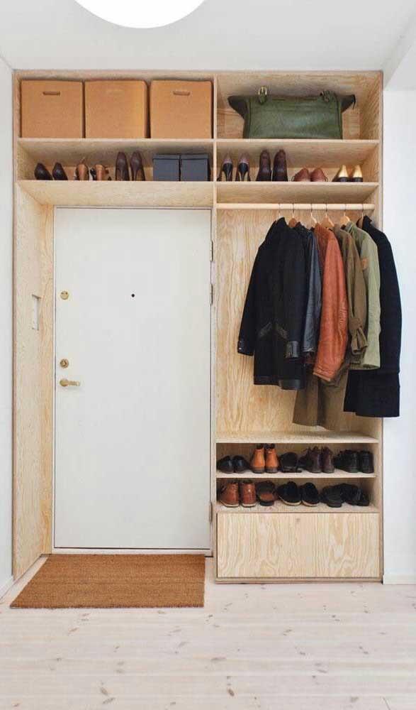 Guarda-roupa aberto feito com madeira de pinus contornando a entrada do quarto