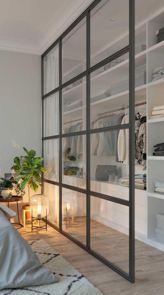 Guarda-roupa aberto separado do restante do quarto pela divisória de vidro