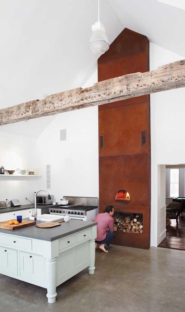 Já nesse espaço rústico, o forno a lenha ganhou destaque graças a faixa de revestimento que o acompanha