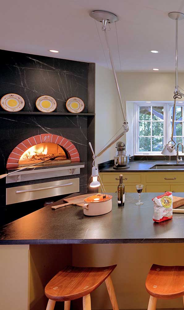 A parede revestida com mármore traz um forno a lenha grande e de acabamento tradicional