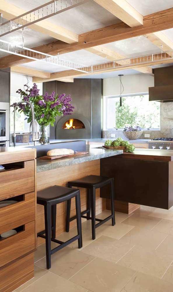 Mesmo lá atrás, no canto da cozinha, o forno a lenha se destaca