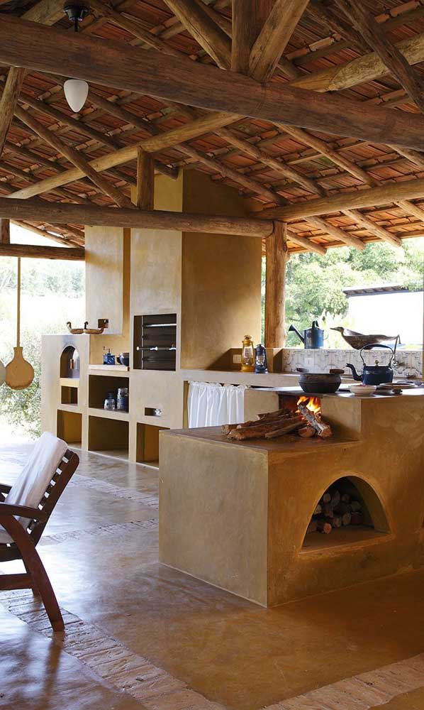 Uma área rústica super convidativa com forno e fogão a lenha integrados
