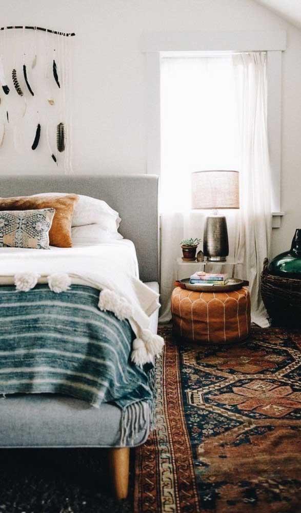 Puff de couro complementando o espaço criado ao lado da cama, no lugar do criado-mudo.