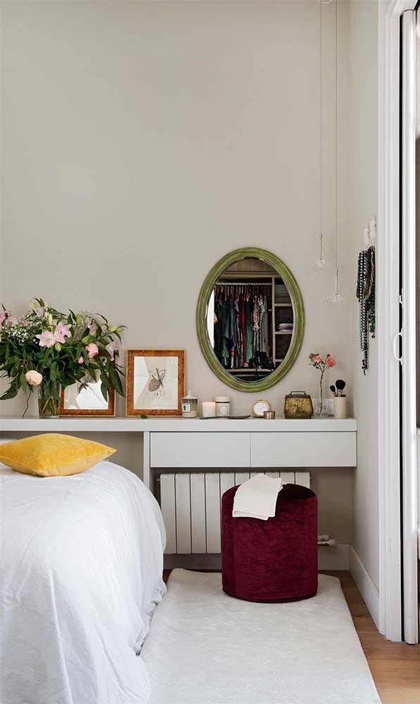 O quarto de casal clean apostou em um puff de veludo cor de vinho para gerar contraste