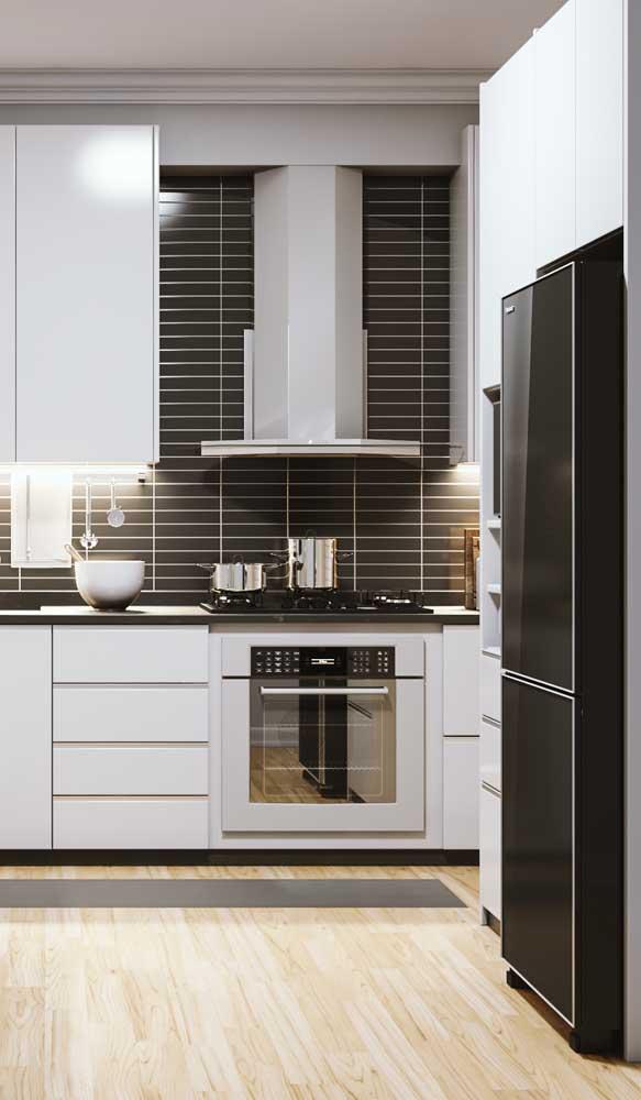 A cozinha de móveis brancos ganhou destaque e personalidade com a geladeira preta moderna
