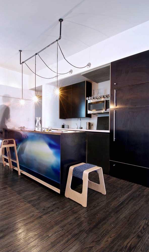 Uma geladeira preta maquiada entre os armários, igualmente pretos, da cozinha