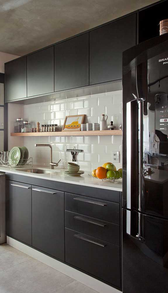 Aqui, a geladeira preta traz continuidade visual aos armários da mesma cor
