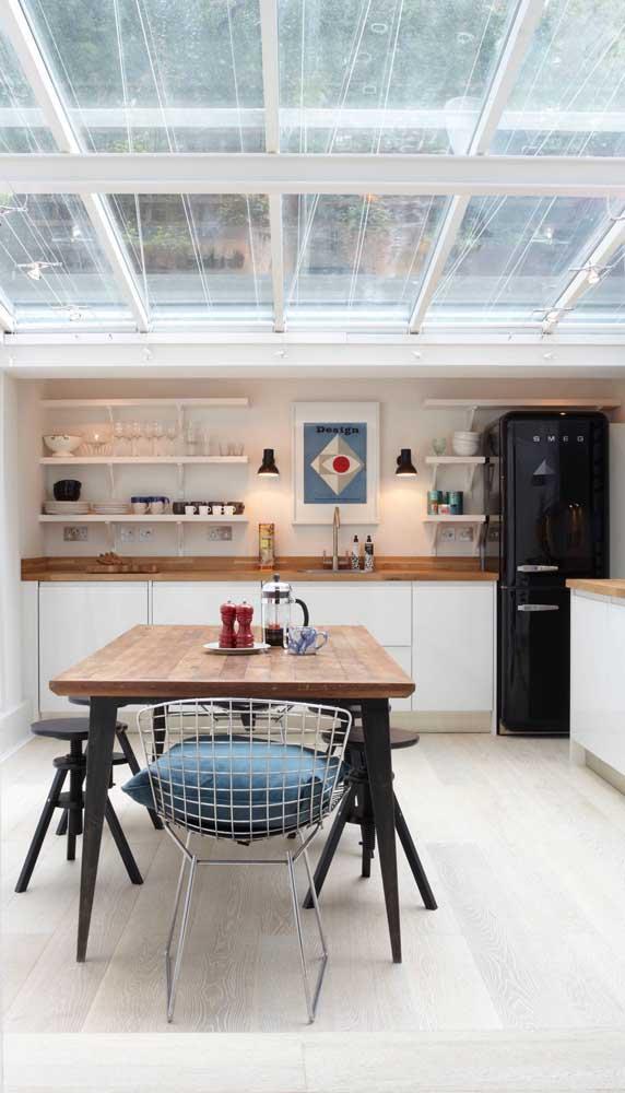A cozinha clean, com um leve toque rústico, apostou sem medo na geladeira preta