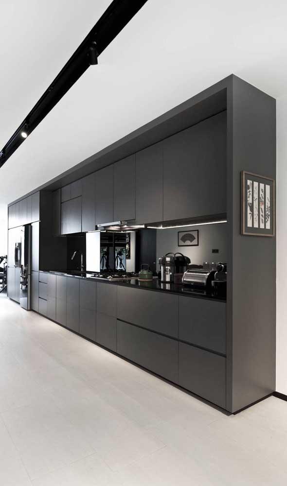 Cozinha de uma parede só! A geladeira preta está ali, entre os armários da mesma cor