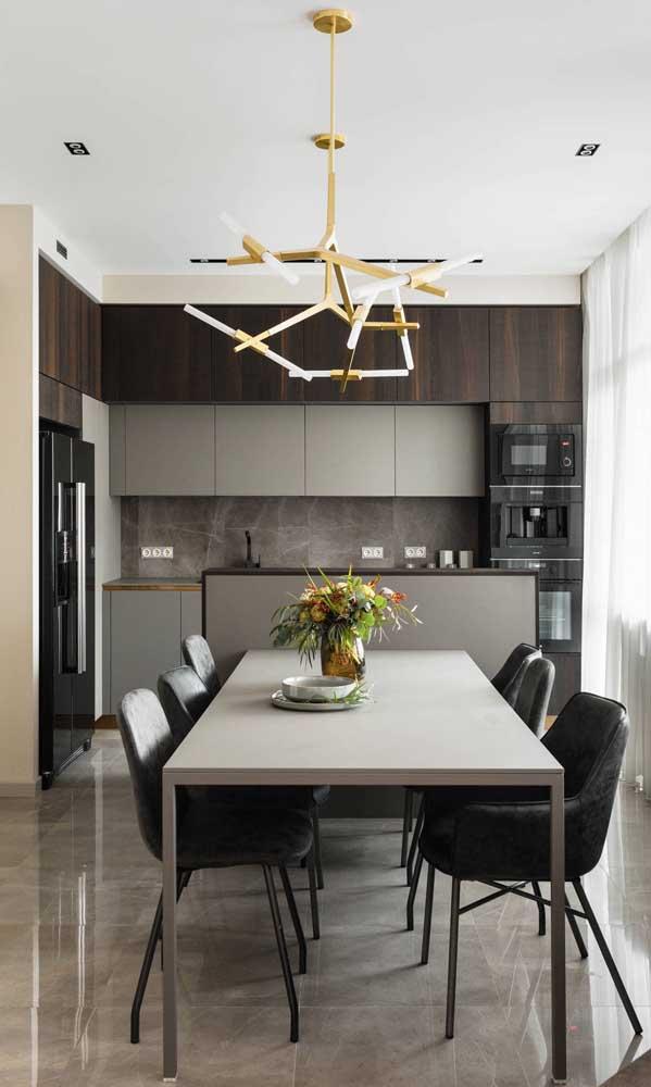 Cozinha em L com eletros pretos combinando com o tom amadeirado dos armários